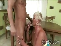 Big blond granny bends on her knees to devour young prick